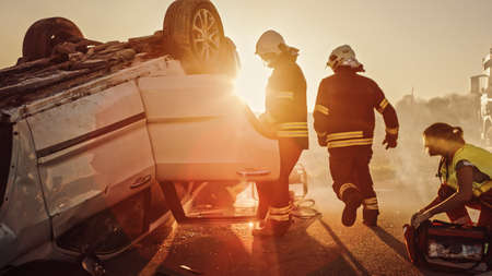 Car Crash Traffic Accident: Paramedics and Firefighters Plan Rescuing Passengers Trapped in Rollover Vehicle. Medics Prepare Stretchers and First Aid Equipment. Firemen Use Hydraulic Cutters Spreader Foto de archivo