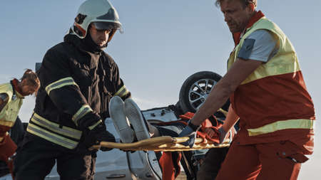 On Car Crash Traffic Accident Scene: Rescue Team of Firefighters Pull Female Victim out of Rollover Vehicle, They Use Stretchers Carefully, Hand Her Over to Paramedics who Perform First Aid. Low Angle Foto de archivo