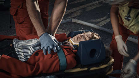 On the Car Crash Traffic Accident Scene: Paramedics Saving Life of a Female Victim who is Lying on Stretchers. They Apply Oxygen Mask, Do Cardiopulmonary Resuscitation CPR and Perform First Aid