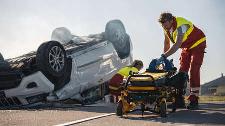 Paramedics and Firefighters Arrive On the Car Crash Traffic Accident Scene. Professionals Prepairing Stretchers For Rescue Injured Victim Trapped in Rollover Vehicle.