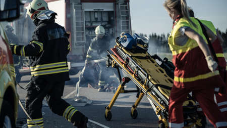 On the Car Crash Traffic Accident Scene: Paramedics and Firefighters Rescue Injured Victims Trapped in the Vehicle. Medics Use Stretchers, Perform First Aid. Firemen Grab Equipment from Fire Engine Archivio Fotografico
