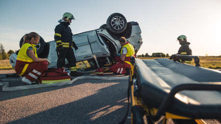 On the Car Crash Traffic Accident Scene: Paramedics and Firefighters Rescue Injured Victim Trapped in the Vehicle. Extricate Person Using Stretchers, Give First Aid and Transport Them to Hospital