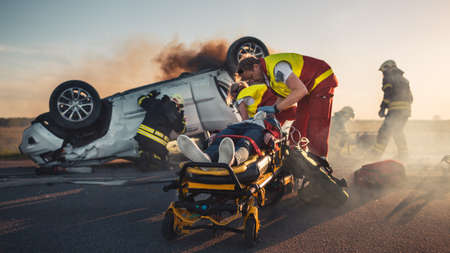On the Car Crash Traffic Accident Scene: Paramedics Save Life of a Female Victim Lying on Stretchers. They Listen To a Heartbeat, Apply Oxygen Mask and Give First Aid. Firefighters Extinguish Fire Foto de archivo