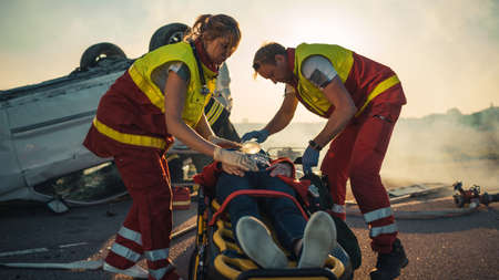 On the Car Crash Traffic Accident Scene: Paramedics Saving Life of a Female Victim who is Lying on Stretchers. They Listen To a Heartbeat, Apply Oxygen Mask and Give First Aid. Background Firefighters Foto de archivo
