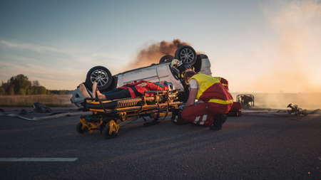 On the Car Crash Traffic Accident Scene: Paramedics Saving Life of a Female Victim who is Lying on Stretchers. Perform First Aid Foto de archivo