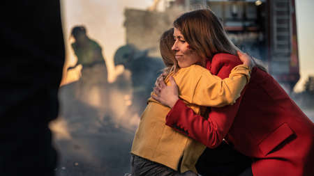 Car Crash Traffic Accident: Injured Young Girl Reunites with Her Loving Mother. In the Background Fire engine and Courageous Paramedics and Firemen Save Lives Foto de archivo