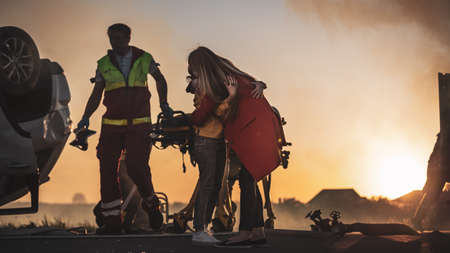 Car Crash Traffic Accident: Injured Young Girl Reunites with Her Loving Mother. In the Background Rollover Car and Courageous Paramedics and Firemen Save Lives