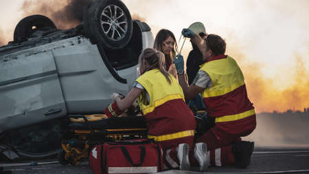 On the Car Crash Traffic Accident Scene: Paramedics Perform First Aid of a Female Victim who is Sitting on Stretchers. They Apply Oxygen Mask.