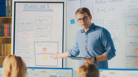 Elementary School Class: Teacher Uses Interactive Digital Whiteboard, Explains Lesson to Diverse Group of Smart Children. Kids getting Modern Education, Learn Computer Science, Software Programming Banque d'images