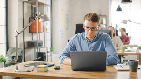 Handsome Young Man in Glasses and Shirt is Working on a Laptop in a Creative Business Agency. They Work in Loft Office. Diverse People Working in the Background. Hes in Good Mood.