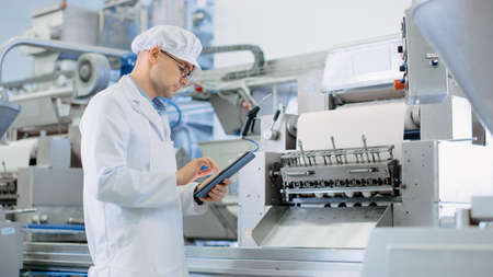 Young Male Quality Supervisor or Food Technician is Inspecting the Automated Production at a Dumpling Food Factory. Employee Uses a Tablet Computer for Work. He Wears White Sanitary Hat and Work Robe. Archivio Fotografico