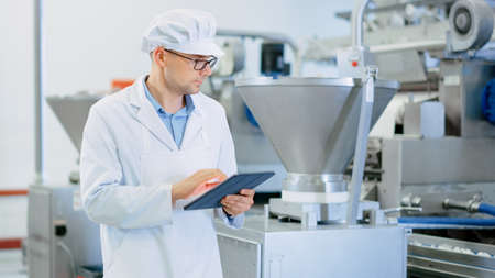 Young Male Quality Supervisor or Food Technician is Inspecting the Automated Production at a Dumpling Food Factory. Employee Uses a Tablet Computer for Work. He Wears White Sanitary Hat and Work Robe.