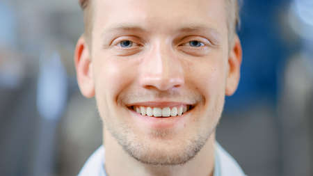 Close Up of a Handsome Young Blond Male Portrait Shot. Hes a Professional Employee. Man Looks and Smiles at Camera. Expresses Success and Happiness. He Has Blue Eyes and Light Beard.