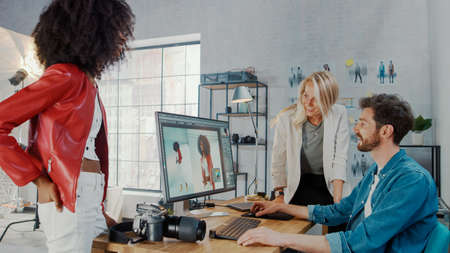 In Photo Studio Fashion Magazine Designer and Beautiful Black Cover Girl talk to a Professional Photographer who Uses Desktop Computer to Retouch Photographs in an Image Editing Software