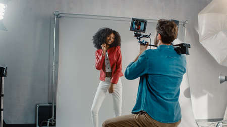 Beautiful Black Model Posing for a Video Clip, Cameraman Filming Her. She plays with Facial Expressions. Stylish Fashion Magazine. Photo Shoot done with Pro Equipment in a Studio Foto de archivo