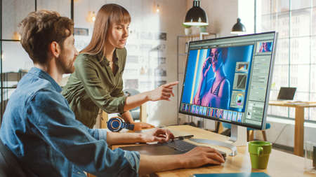 Female Art Director Consults Designer Colleague, They Work on a Portrait in Photo Editing Software. They Work in a Cool Office Loft. They Look Very Creative and Cool. Stock Photo