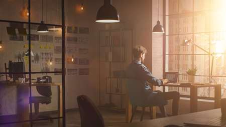 Handsome Creative Developer Works on a Laptop in His Studio. Designing Apps and Social Media Design Structure in His Sunny Loft Office. Modern Urban City View from the Window.
