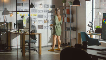 Young Creative Woman Stands Next to the Wall with Organized Mood Board in His Cool Loft Office. She Takes Notes on a Piece of Paper. Sunny Day Outside the Window.