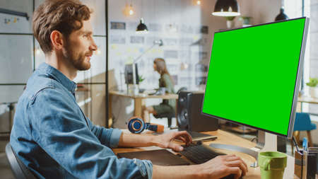 Male Creative Designer with Beard and Jeans Shirt Works on His Personal Computer with Big Green Screen Mock Up Display. He Works in Cool Office Loft. Female Creative Colleague Works in Background. Banque d'images