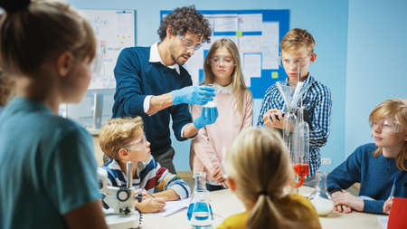 Elementary School Science Classroom: Enthusiastic Teacher Explains Chemistry to Diverse Group of Children, Shows them How to Mix Chemicals in Beakers. Children UseSafety Glasses and Talk