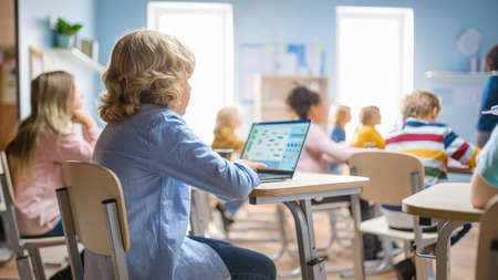 Elementary School Science Class: Little Boy Uses Laptop with Screen Showing Programming Software. Physics Teacher Explains Lesson to a Diverse Class full of Smart Kids. Over the Shoulder Shot. Banco de Imagens