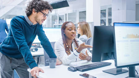 In the Busy Corporate Office: Manager Talks to Businesswoman who Works on Desktop Computer. Businesspeople an Working with Clients, Having Discussions and Analysing Statistics