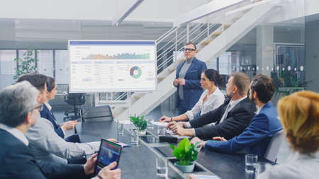 In Corporate Meeting Room: Creative Director Uses Digital Interactive Whiteboard for Presentation to Board of Executives, Lawyers, Investors, Businesspeople. Screen Shows Company Growth Data