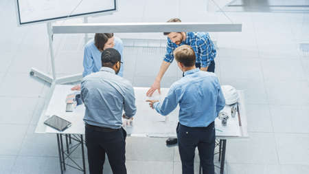 In Busy Engineering Facility: Diverse Group of Engineers, Technicians, Specialists Working on Design for Industrial Engine Prototype. Professionals Talk, Work with Drawings, Use Computers. High Angle