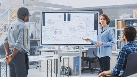 In Industrial Design Facility Team of Engineers and Technicians have a Meeting, Female Specialist Leads Briefing, Talks and Draws on Digital Interactive Whiteboard with Car Prototype Concepts Banque d'images