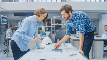 In the Industrial Engineering Facility: Young Female Designer Works with Chief Industrial Engineer, They have Discussion, Analyse and Correct Engine Design Technical Drafts that are Lying on the Table