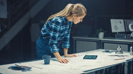 In the Dark Industrial Design Engineering Facility: Female Engineer Works with Blueprints Laying on a Table, Uses Digital Tablet and Drinks Coffee. On the Desktop Drawings and Engine Components