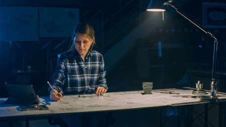 Female Engineer Sitting at Her Desk Works with Blueprints Laying on a Table, Uses Pencil, Ruler and Digital Tablet. In the Dark Industrial Design Engineering Facility