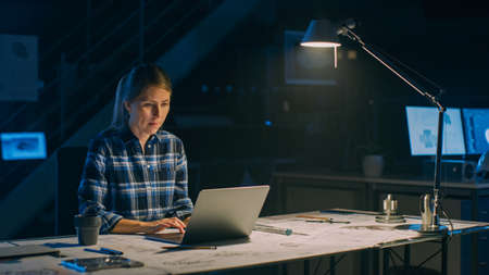 Beautiful Female Engineer Sitting at Her Desk Works on a Laptop Computer. Blueprints Lying on a Table. In the Dark Industrial Design Engineering Facility. Warm Light Lamp Banco de Imagens