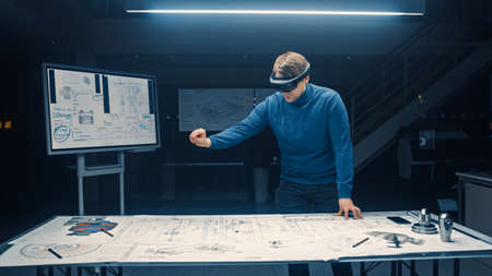 Software Development Engineer Wearing Virtual Reality Headset Gestures and Manipulates Components in Augmented Reality. Engineering Facility Has Desk with Engine and Car Concept Blueprints Banco de Imagens