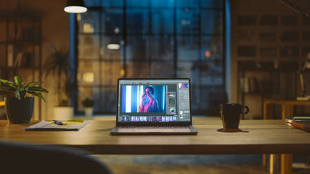 Shot of a Laptop Computer in the Modern Office Showing Photo Editing Software. In the Background Warm Evening Lighting and Open Space Studio with City Window View Stock Photo