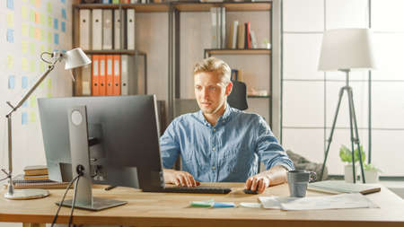 Creative Entrepreneur Sitting at His Desk Works on Desktop Computer in the Stylish Office. Handsome Young Businessman Uses Computer, Does Outsourcing Job, Designs New Apps and Develops Software