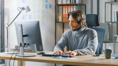 Handsome Long Haired Entrepreneur Sitting at His Desk in the Office Works on Desktop Computer, Working with Documents, Charts, Graphs, Statistic and Strategy. Creative Entrepreneur Using Computer Stockfoto