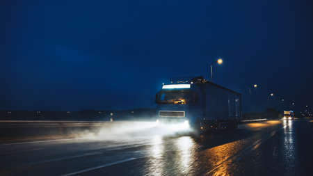 Blue Long Haul Semi-Truck with Cargo Trailer Full of Goods Travels At Night on the Freeway Road, Driving Across Continent Through Rain, Fog, Snow. Industrial Warehouses Area. Front Shot Stock Photo