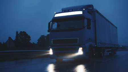Long Haul Semi-Truck with Cargo Trailer Full of Goods Travels on Highway Road. Driving in Early Morning Across Continent Through Rain, Fog. Industrial Warehouses Area.