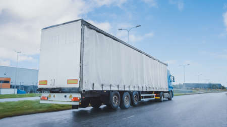 Long Haul Semi-Truck with Cargo Trailer Full of Goods Travels on the Highway Road. Daytime Driving Across Continent Through Rain, Fog. Industrial Warehouses Area.