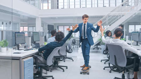 Young Happy Handsome Manager Wearing a Suit and Tie Rides a Longboard. Giving High Fives to Colleagues. Diverse and Motivated Business People Work on Computers in Modern Open Office. 版權商用圖片