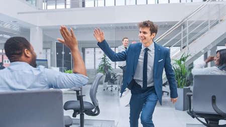 Young Happy Business Manager Wearing a Suit and Tie Dancing and Giving High Fives in the Office. Celebrating Success. Diverse and Motivated Business People Work on Computers in Modern Open Office.