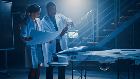 Two Aerospace Engineers Work On Unmanned Aerial Vehicle Drone Prototype. Aviation Scientists in White Coats Holding Blueprints. Laboratory with Commercial Aerial Surveillance Aircraft Reklamní fotografie