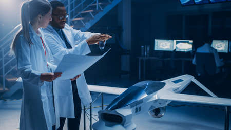 Two Aerospace Engineers Work On Unmanned Aerial Vehicle Drone Prototype. Aviation Scientists Talking, using Blueprints. Industrial Laboratory with Commercial Aerial Surveillance Aircraft