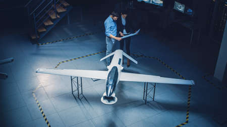 Meeting of Aerospace Engineers Work On Unmanned Aerial Vehicle Drone Prototype. Aviation Experts have Discussion. Industrial Facility with Aircraft Capable of GPS Surveillance and Military Missions