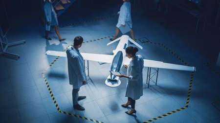 Two Aerospace Engineers Work On Unmanned Aerial Vehicle Drone Prototype. Aviation Scientists in White Coats Talking, Using Tablet Computer. Industrial Laboratory with Surveillance or Military Aircraft