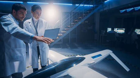 Meeting of Aerospace Engineers Working On Unmanned Aerial Vehicle Drone Prototype. Aviation Scientists in White Coats Talking. Commercial Aerial Surveillance Aircraft in Industrial Laboratory