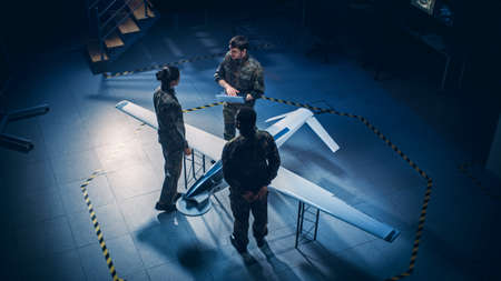 Army Aerospace Engineers Work On Unmanned Aerial Vehicle Drone. Uniformed Aviation Experts Talk, Using Laptop. Industrial Facility with Surveillance, Warfare Tactics, Attack Machine. Elevated Shot