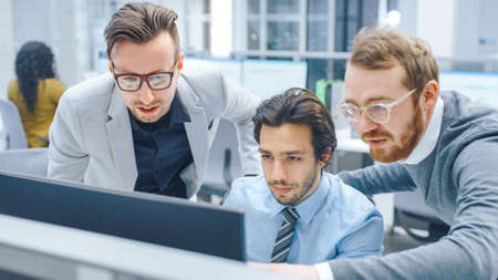 In Bright Modern Office: Businessman Sitting and Working at His Desktop Computer, Project Manager and Team Leader Standing Beside Him. They Have Discussion, Find Problem Solution, Pointing at Screen