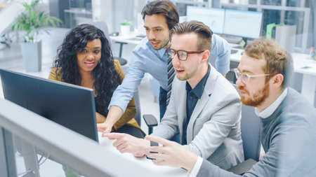 In Modern Office: Diverse Team of Businessmen and Businesswoman Work on Computer, Having Discussion, Successfully Finding Problem, Applaud and Cheerfully Celebrate. Happy and Motivated Businesspeople Foto de archivo